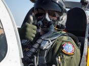 Author (User:BQZip01) in a jet wearing appropriate flight gear to include an MBU-20 oxygen mask, helmet, flight suit, flight gloves, and parachute.