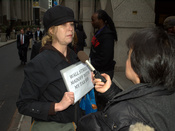 English: A protester outside AIG's headquarters at the American International Buildling in New York City is interviewed by a news crew. Photographer's blog post about this photo.