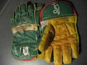 A pair of wicket-keeping gloves. The webbing which helps the keeper to catch the ball can be seen between the thumb and index fingers.