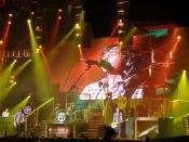 English: perform at The Point, as part of their ' tour. is behind the piano (left), on the drums, on the bass (right), and on guitar (left and screen).