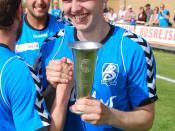 Dansk: Fodboldspilleren Jonas Westmark fra Blokhus FC. Her med pokalen som vinder af 2. division Vest, samtidig med han giver hånd til Christian Overby, efter kampen mod Varde IF på Jetsmark Stadion i Pandrup.