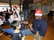 English: SASEBO, Japan (Dec. 18, 2009) Religious Program Specialist 2nd Class Josia Onyango plays with a child during a holiday community service project at the Kusuzumi daycare center where Sailors from Fleet Activities Sasebo played with the children an