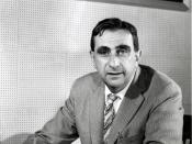 Edward Teller, in 1958, as Director of Lawrence Livermore National Laboratory. Note that the picture at his top left is of the Alpha Calutron Racetrack from the Manhattan Project, and the picture at his top right is of the 1953 BADGER nuclear test. Image