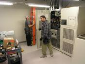 English: Large UPS (Uninterruptible Power Supply) being installed in a Datacenter. This unit has a 500kVA capacity. Electricians provide scale for size.