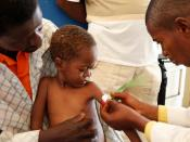 Medical staff examine a child for signs of malnourishment in DRC