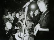 Warner Bros. promotional picture of the Sex Pistols, in performance at the 100 Club, 1976. On the right: Steve Jones (foreground) and Johnny Rotten (background)..