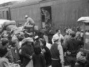 Los Angeles, California. Japanese Americans going to Manzanar gather around a baggage car at the old Santa Fe Station. (April 1942)[59]. Japanese Americans boarding a train bound for one of ten American concentration camps.
