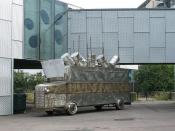 English: I accuse the oil companies... When I first saw the slogan on the side of this splendid mock armoured vehicle in the grounds of the Stephen Lawrence centre I thought it had been prepared for 'climate change' protests, but then I saw the name Ken S
