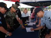 US Navy 070614-N-3390M-001 Religious Program Specialist 2nd Class Delmar Ramirez, right, visits Naval Station Everett^rsquo,s security department recruiting booth at a job fair held at the Smokey Point Naval Support Complex dur