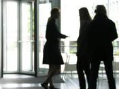English: University students communicate. Two women and a man in the college lobby. Deutsch: Zwei Studentinnen unterhalten sich, ein Student steht breitbeinig daneben und schaut zu.