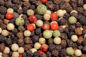 English: A mixture of black peppercorns from the Malabar Coast, white Muntok peppercorns from Bangka, China, green peppercorns from Brazil, and pink peppercorns (berries of the Baies rose plant, Schinus terebinthifolius) from Réunion (France). Packaged as