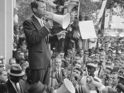 Attorney General Robert F. Kennedy speaking to a crowd of African Americans and whites through a megaphone outside the Justice Department; sign for Congress of Racial Equality is prominently displayed.