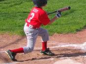 English: A Little League baseball player squares around to bunt.