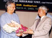 English: Mr. Ghulam Mustafa, President, Chittagong University Ex-Economics Students Association (CUEESA) presenting bouquette to Prof. Muhammed Yunus, Founder Managing Director of world-famous Grameen Bank and Micro-Credit Concept at BIAM Auditorium on Ma