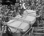 People on Nias Island in Indonesia move a megalith to a construction site, circa 1915. Digitally restored.