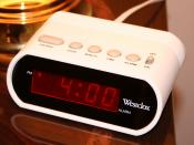 A typical digital 12-hour alarm clock indicating p.m. with a dot to the left of the hour