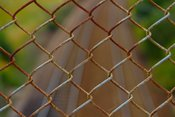 English: A pice of chain link fence over some railroad tracks