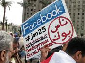 English: A protester holding a placard in Tahrir Square referring to Facebook and Twitter, acknowledging the role played by social media during the 2011 Egyptian Revolution.