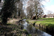 English: Beddington: River Wandle, looking west As the River Wandle runs out of Croydon and into Sutton, it emerges into the open air from the culvert system that has carried it under Croydon. The Wandle here is carrying excess water from Waddon Ponds as