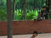 Begging, only money to think about - a child caring for a child in poverty, beautiful garden at জাতীয় স্মৃতি সৌধ Jatiyo Smriti Soudho Independence memorial park, Savar, Dhania, Dhaka, Bangladesh