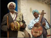 Village musicians in Hyderabad singing and playing a drum and string instrument. The latter is decorated with swastika and aum signs.