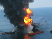 English: Platform supply vessels battle the blazing remnants of the off shore oil rig Deepwater Horizon. A Coast Guard MH-65C dolphin rescue helicopter and crew document the fire aboard the mobile offshore drilling unit Deepwater Horizon, while searching