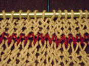 Knitted fabric showing a single red course of plaited stitches. The five stitches to the right of the blue needle at the top were knit into the back loop to twist the stitches one way; the five to the left of the same needle were knit by wrapping the yarn