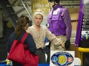 An employee from the Office of Naval Research (ONR) Tech Solutions program explains an improved flight deck uniform to a visitor.