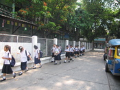 English: In Bangkok, these students were returning from their lunch break. Their school was next to a temple that we were visiting.
