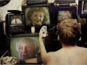 Lukas uses several television sets to absorb as many Holocaust survivor testimonies as possible. The people seen are actual Holocaust survivors.