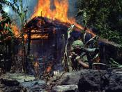 U. S. soldier carries a M67 recoilless rifle past a burning Viet Cong base camp in Mỹ Tho, South Vietnam, 1968