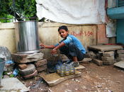 English: Wasim, a child labourer, works at a tea stall in Indore, India. His work is to serve tea/coffee and wash glasses and other utensils.He received daily pay. He is able to read and write, having attended school in the past.