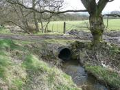 English: Culvert under field access, Glovershaw, Bingley The modern way to bridge a stream; stone and soil over a large plastic pipe, corrugated for extra strength.