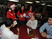 English: YOKOSUKA, Japan (Dec. 22, 2008) Volunteers from the National Honor Society at Kinnick High School pass out Christmas cards to the crew of the aircraft carrier USS George Washington (CVN 73). The cards were donated to the Red Cross from high schoo
