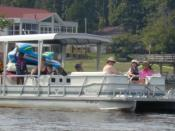 A pontoon boat approaches on Lake Gaston, VA-NC with choir and friends from Genesis UMC of Cary, North Carolina. Two rafts sit on the back of the boat above the engine. Photo by James E. Scarborough July 10, 2004.