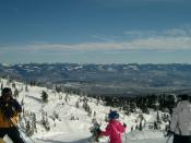 English: Looking out towards the Monashee mountains at the top of the Powder Chair, Big White Ski Resort. People in fore ground are skiers who have just disembarked from the lift. Chairlift in distance is Ridge Rocket Express.