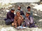 English: Students sit in the boys section of a school in Bamozai, near Gardez, Paktya Province, Afghanistan. The school has no building; classes are held outside in an orchard.