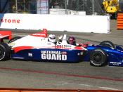 English: TV personality Huell Howser rides as a passenger in a 2-seat Indy Racing League open-wheel race car at the 2009 Long beach Gran Prix.