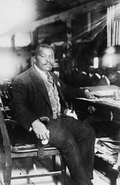 Marcus Garvey, National Hero of Jamaica, full-length, seated at desk