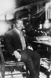 Marcus Garvey, National Hero of Jamaica, full-length, seated at desk