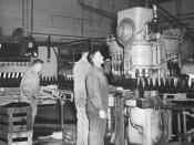 Black and white photo of a bottling machine in operation as part of an Australian beer production operation.
