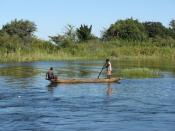 English: 2 locals in a canoe in the Zambezi river