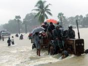 English: People with a few umbrellas cluster onto a tractor in rain and flood water. Original caption: Due to the UN & international NGOs leaving the Vanni on 15 September, TRO is the only large NGO (there are several district based NGOs) working for