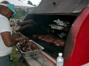English: A barbecue on a trailer at a block party in Kansas City. Pans on the top shelf hold hamburgers and hot dogs that were grilled earlier when the coals were hot. The lower grill is now being used to slowly cook pork ribs and