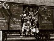 English: German soldiers, some with flowers others waving or rasing their clenched fists, in a railroad car on the way to the front during early World War I (1914). Messages on the car spell out (approximately):