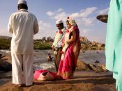 A Muslim couple being wed alongside the Tungabhadra River at Hampi, India. In the background, a Hindu man is taking his ritual bath.