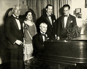 English: Birthday party honoring Maurice Ravel, New York City, March 8, 1928. From left: Oscar Fried, conductor; Eva Gauthier, singer; Ravel at piano; Manoah Leide-Tedesco, composer-conductor; and composer George Gershwin.