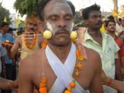 "English: Hindu devotee with garland of marigolds around his neck, a trident piercing two lemons and his cheeks. Original caption: ""Pierced for Peace"" A devotee participating in a religious procession with his cheeks pierced with a sharp trident"
