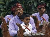 English: Child learning to play in a gamelan orchestra Nederlands: Dia. Theoretische muzieklessen zijn er voor dit kleine Balinese jongetje niet bij. Op de schoot van zijn vader zit hij tussen de andere spelers in het orkest. Af en toe mag hij het hamertj