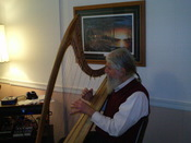 English: A musician playing a harp.